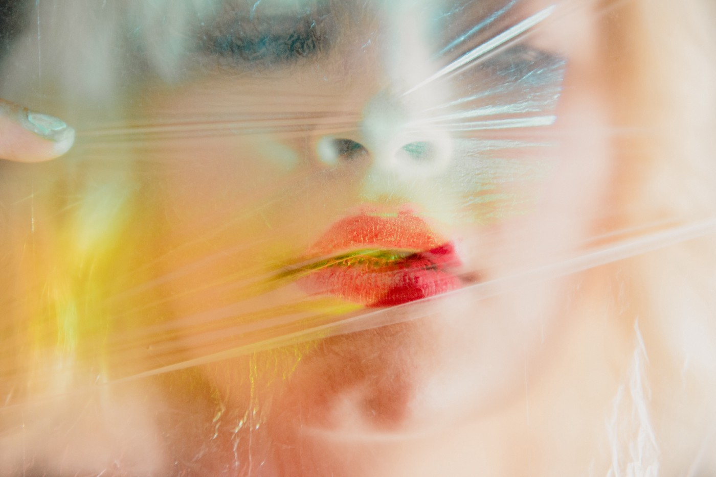Blond woman behind a sheet of plastic, lipstick smeared.
