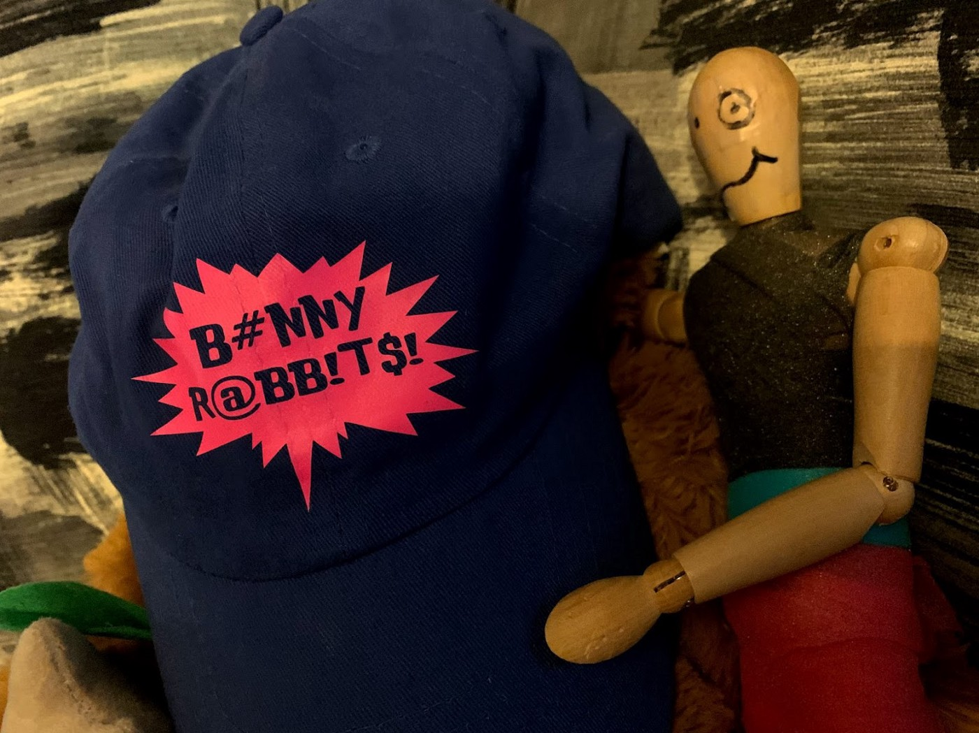 """A mannequin sits next to someone with a baseball cap that reads """"bunny rabbits!"""""""
