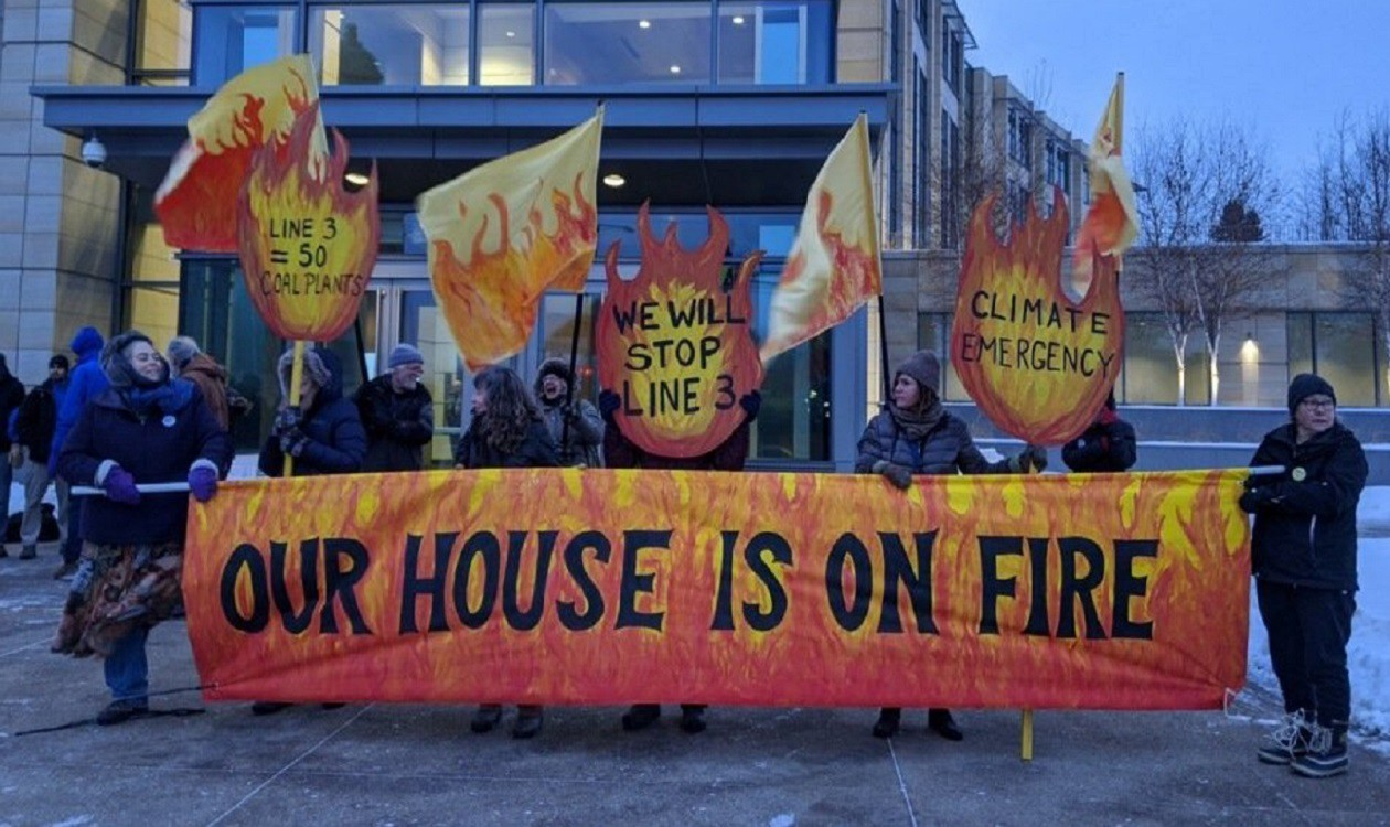 "Activists stand behind a fiery-red banner that reads, ""Our house is on fire."" They hold up signs about the Line 3 pipeline."