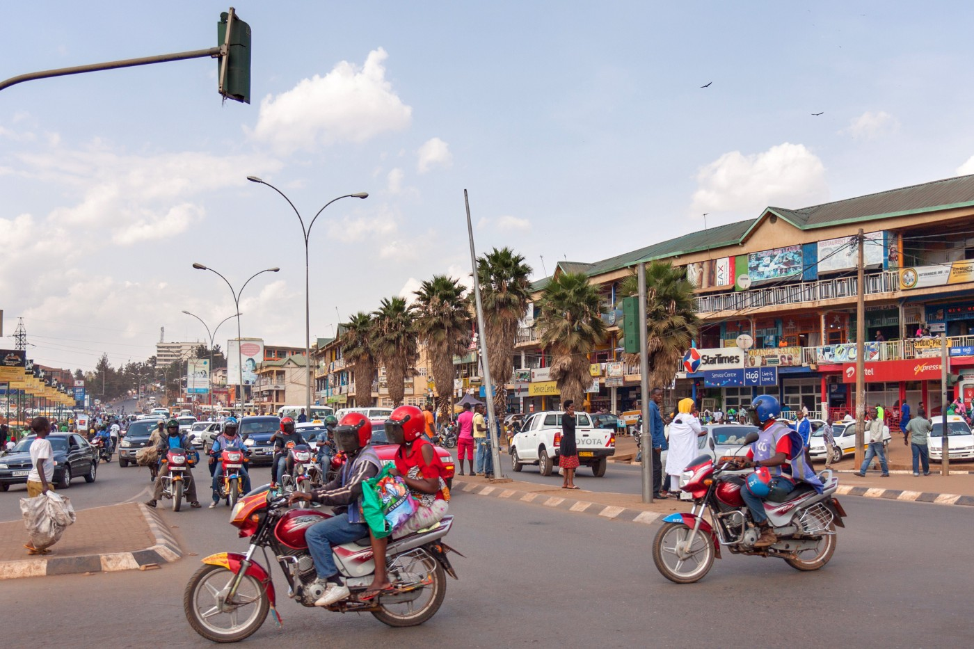 Two motorcycles cross a busy intersection in Kigali, Rwanda