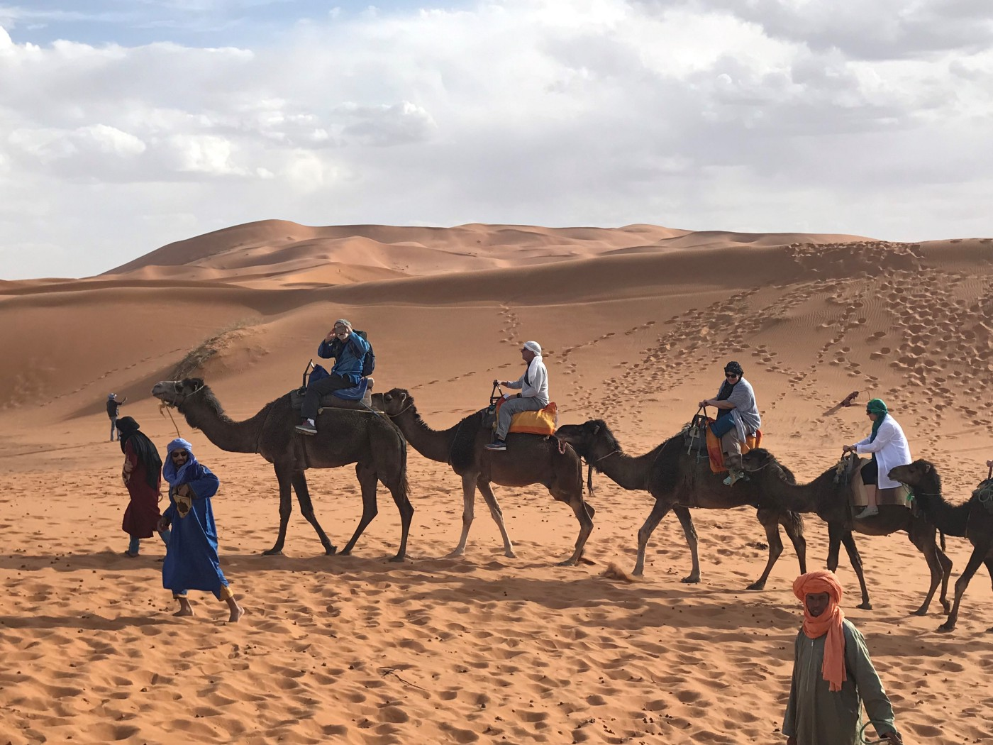 Four people riding camels in the desert with three people walking beside them.