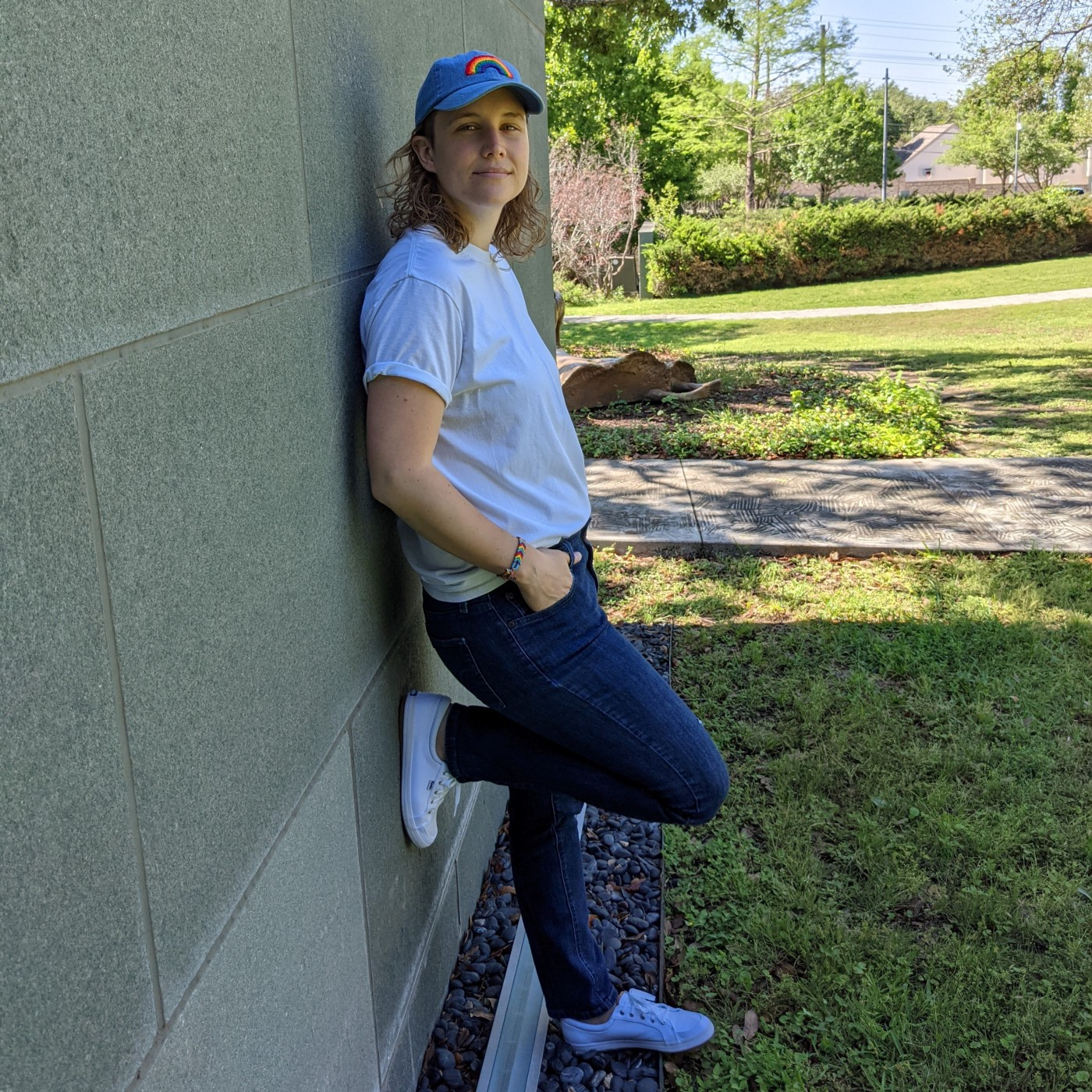 Montana, in a white t-shirt, jeans, white keds, and denim baseball cap embroidered with a rainbow, leans against a grey stone wall