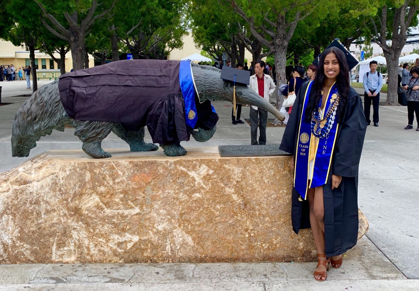 A picture of me, Ami, in my graduation attire in front of an Anteater statue.