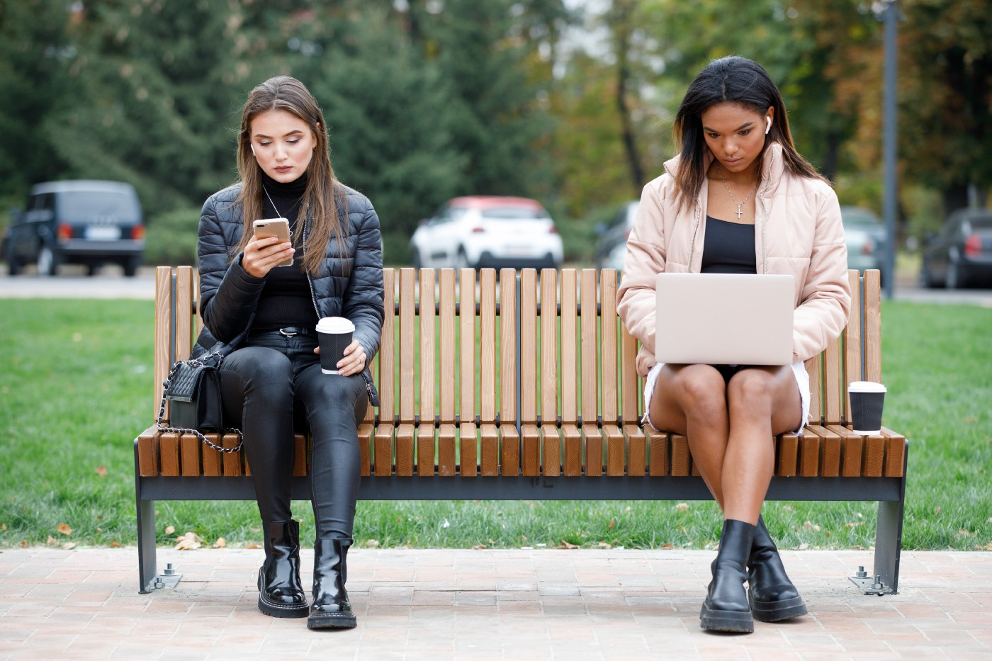 Two women sitting on a park bench paying no attention to each other