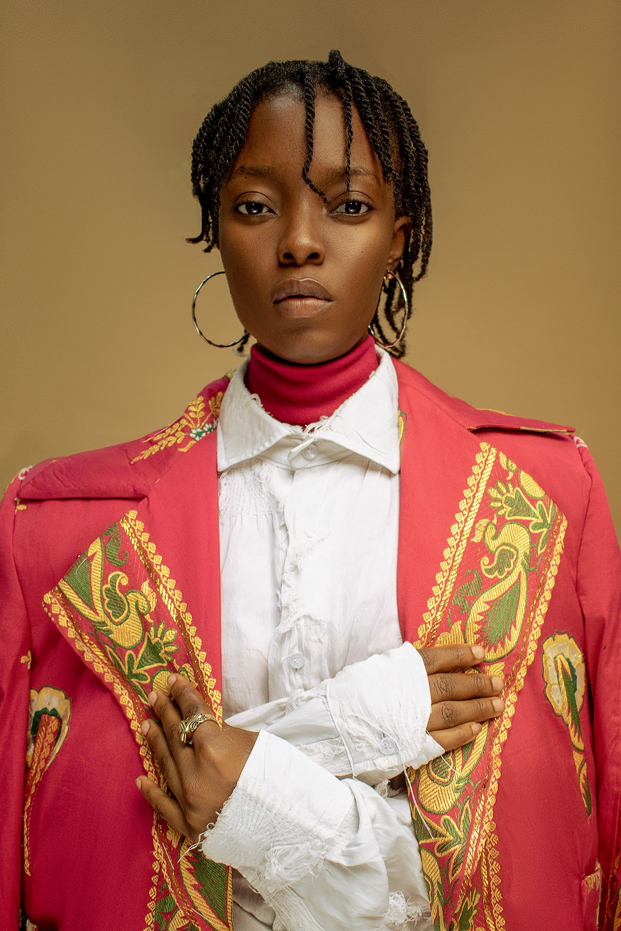 Young black woman in dreadlocks wearing a red uniform-looking clothing
