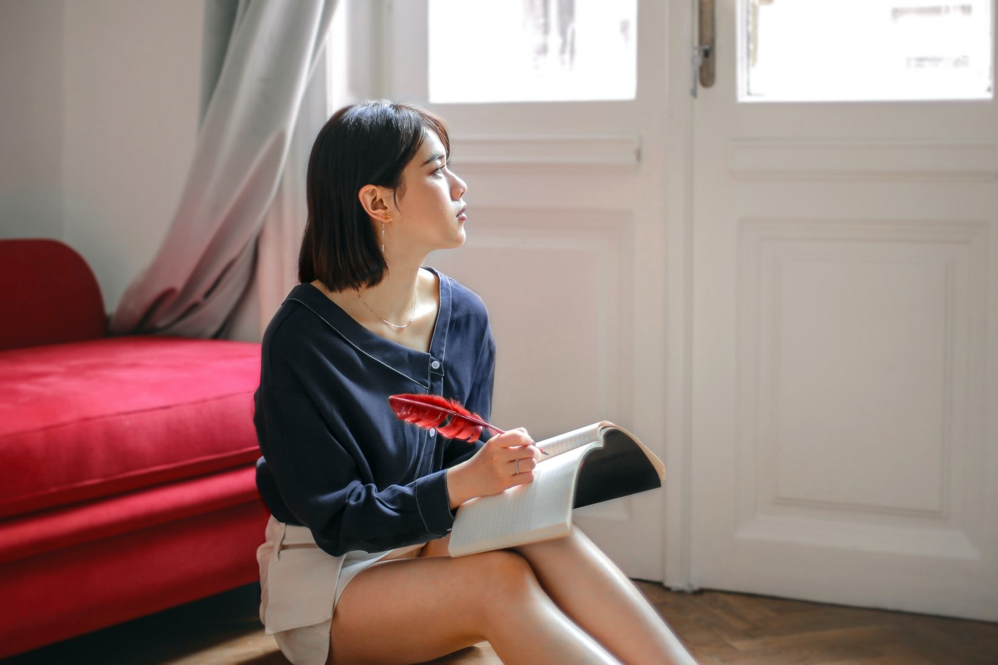 Young woman holding a notebook and feather pen, staring out the window in thought.