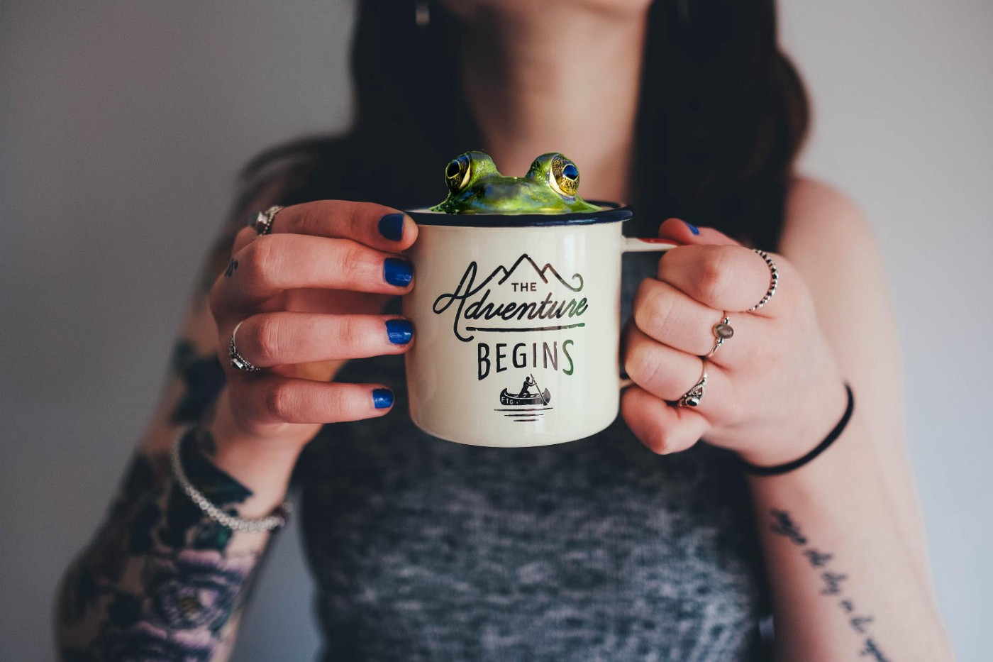 """A tattooed woman holds a coffee mug with """"The Adventure Begins"""" written on it. A frog is peeking out of the top of the mug."""