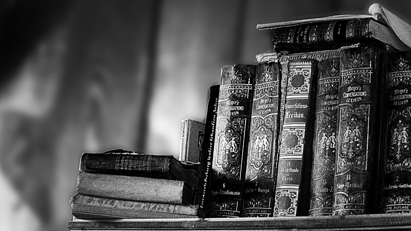 A greyscale picture of a few old books on a shelf—signifying wisdom.