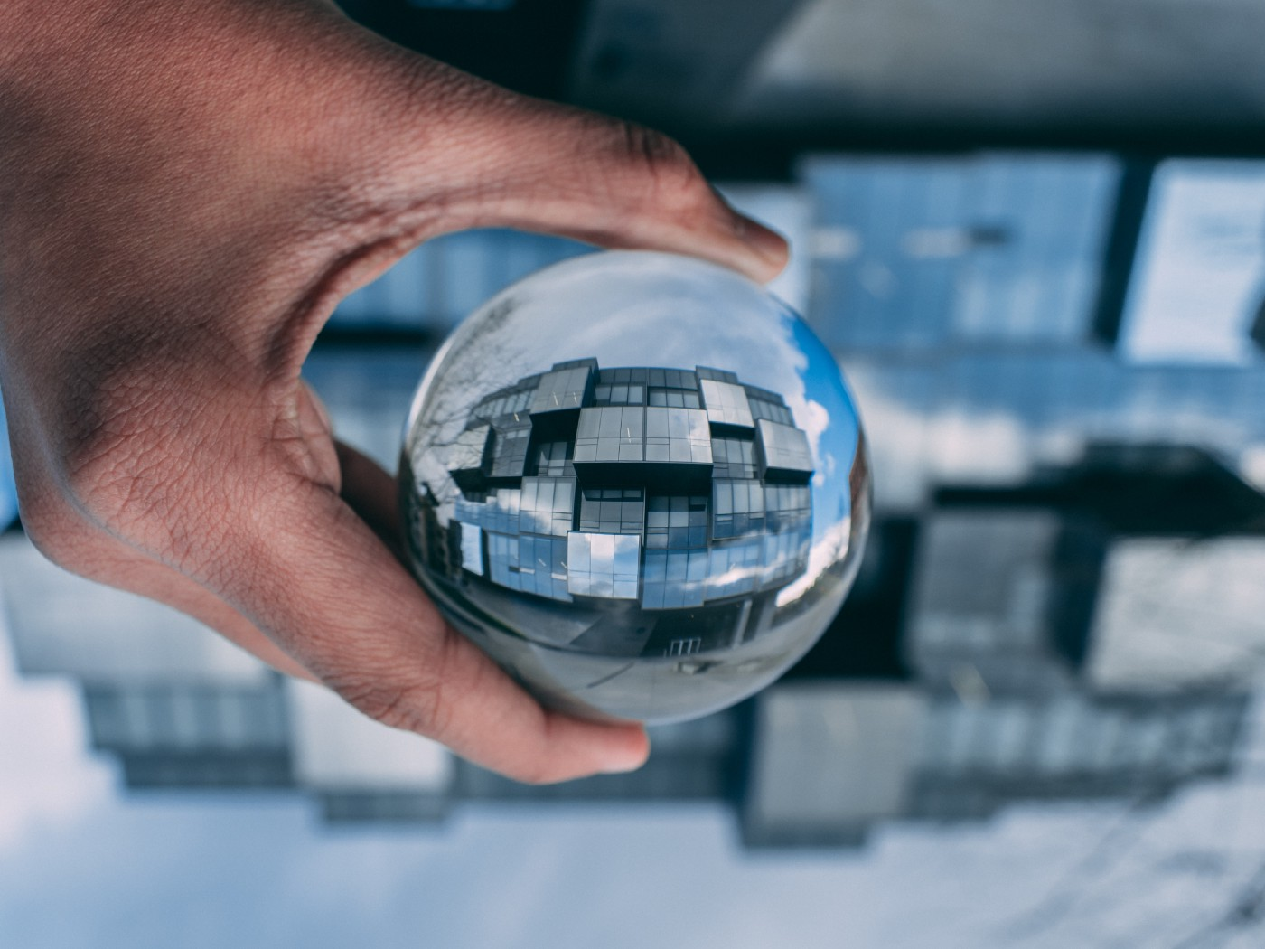 A hand holding a glass ball, which shows a focused mirror image of the blurry glass building behind it.