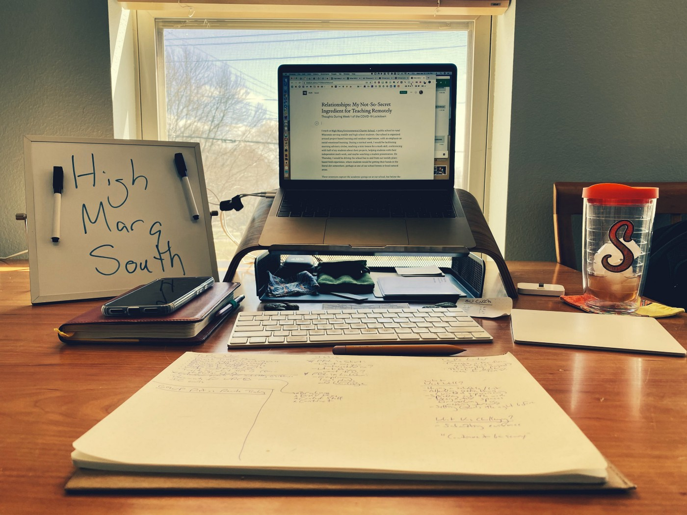 A laptop computer and various desk accessories laid out on a dining room table in front of a window