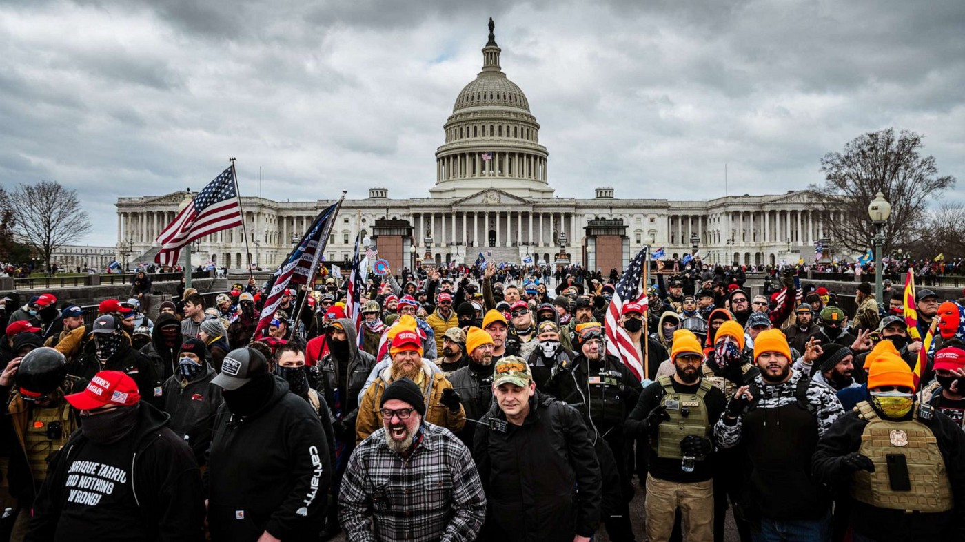 U.S. capitol insurrectionists wave American flags dressed in military gear, gather in front of the U.S. capitol building. One person in front is screaming with rage.
