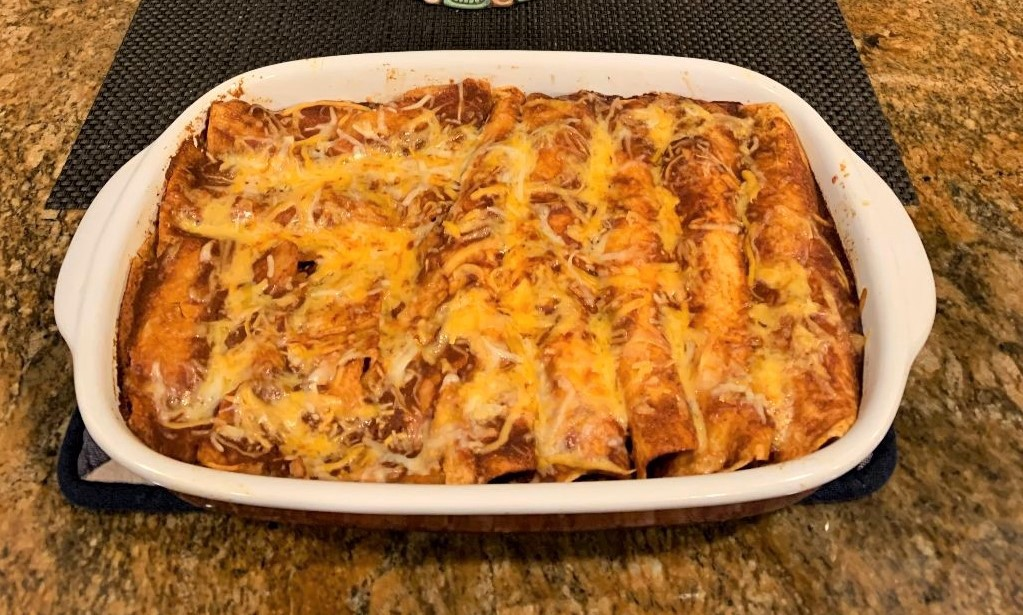 A finished dish of wild turkey enchiladas rests on a counter