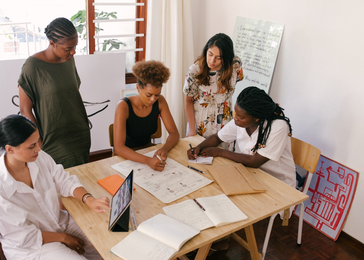 A group of five women sit and stand around a table as they collaborate on product wireframes.