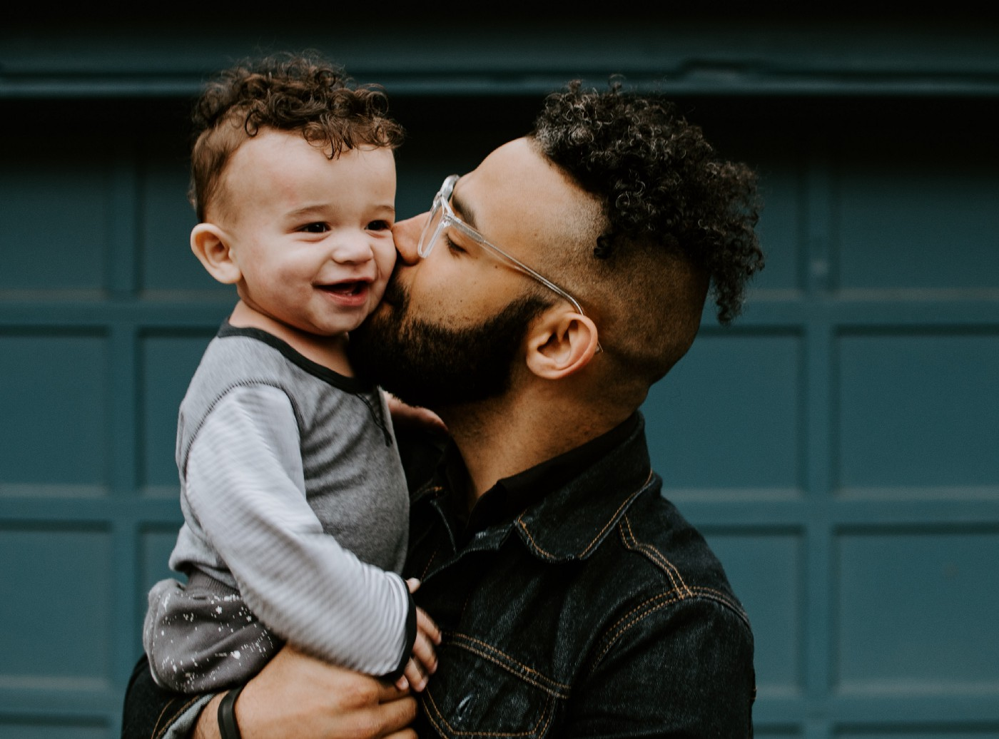 A man kissing a young, smiling child on the cheek