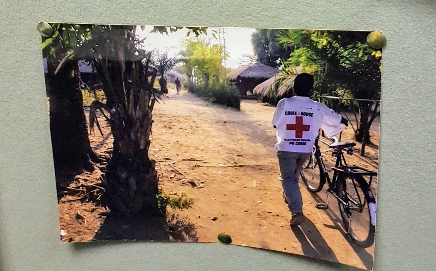 Image of a photo pinned to a noticeboard. The photo shows a man in red cross uniform arriving at a rural village.