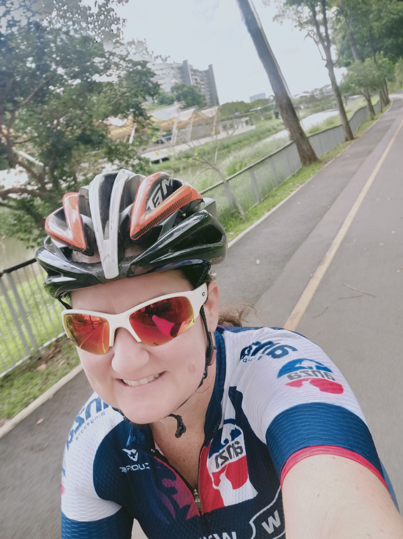 A selfi of a smiling woman wearing a cycling helment and sunglasses