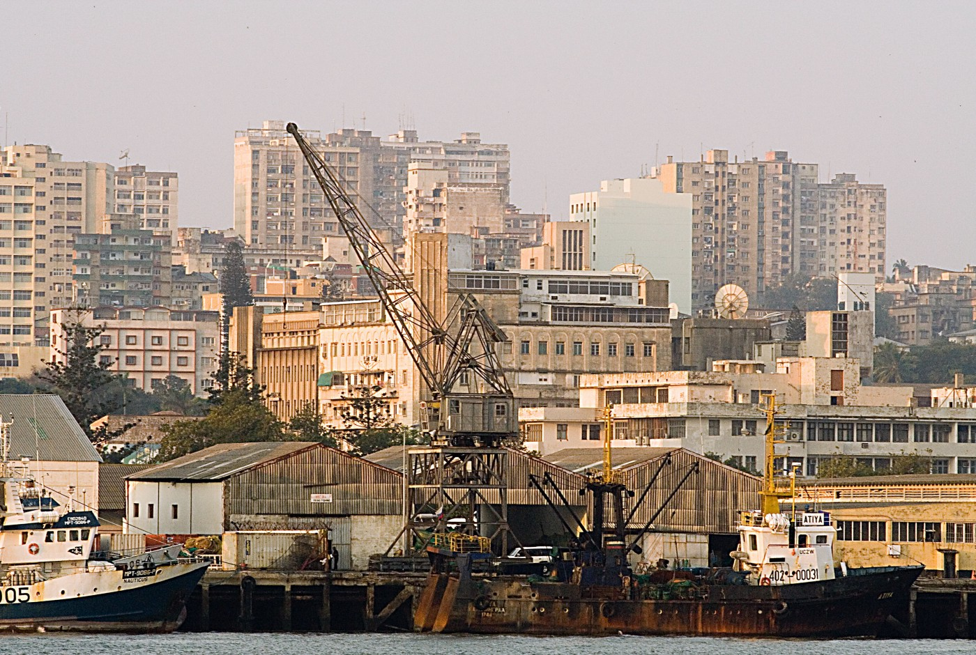 A crowded city skyline with an industrial port in the foreground.