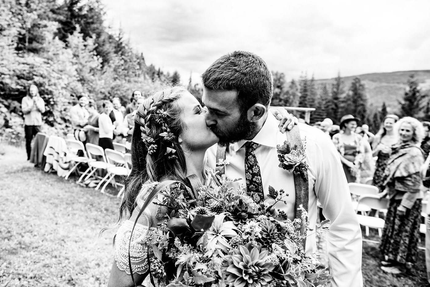 A black and white photo of the author kissing her husband on their wedding day.