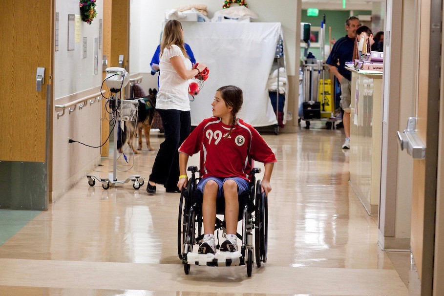 Mackenzie is 11 years old, in a wheelchair, rolling down the hallway of a hospital. Mackenzie is wearing the red soccer jersey she wore when she was injured. Her brown hair is in two braids.