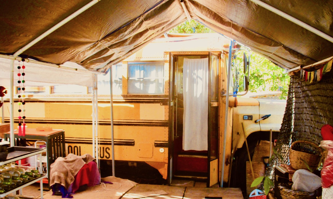 Yellow school bus front entrance with tarp as extension.