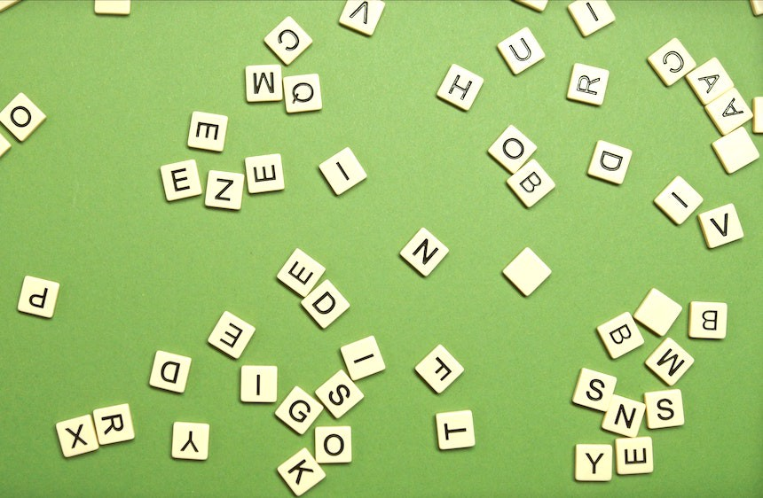 Scrabble letters thrown onto a mid-green background.