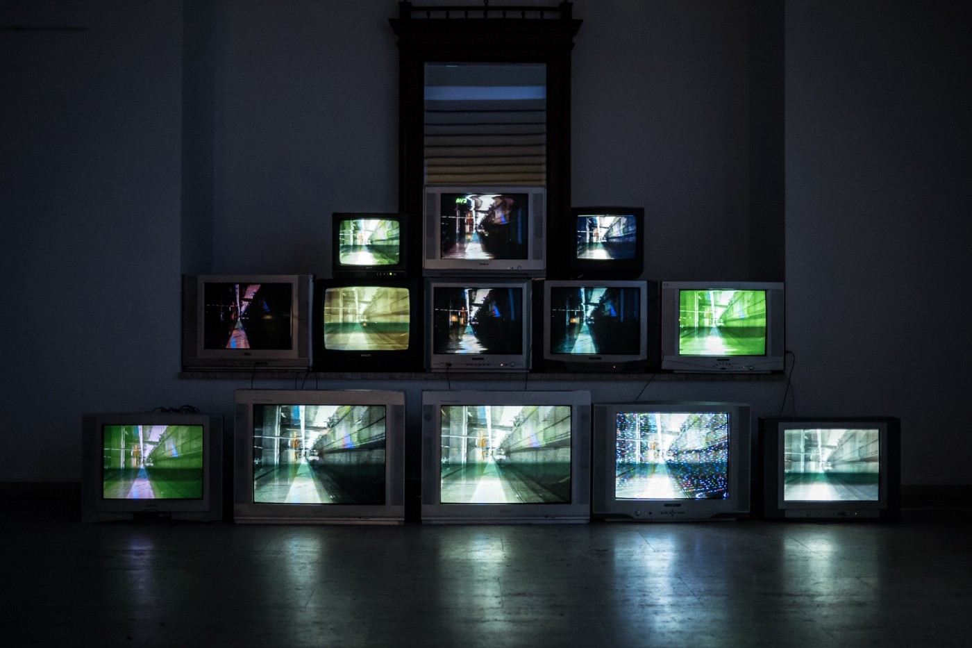 A pyramid of televisions showing the same blurred image in different colours.