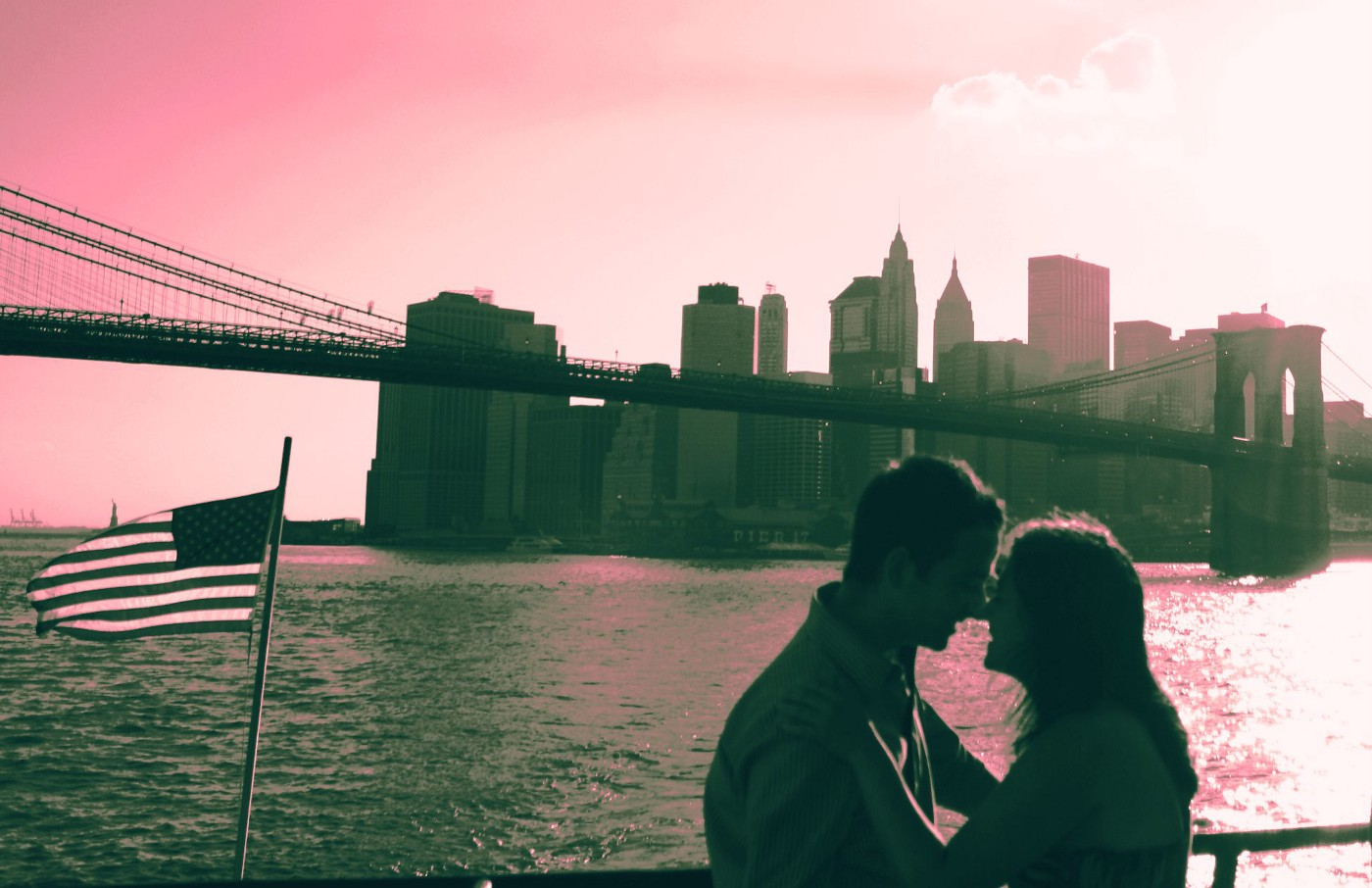 A photo of a couple standing by the water overlooking a bridge and a city.