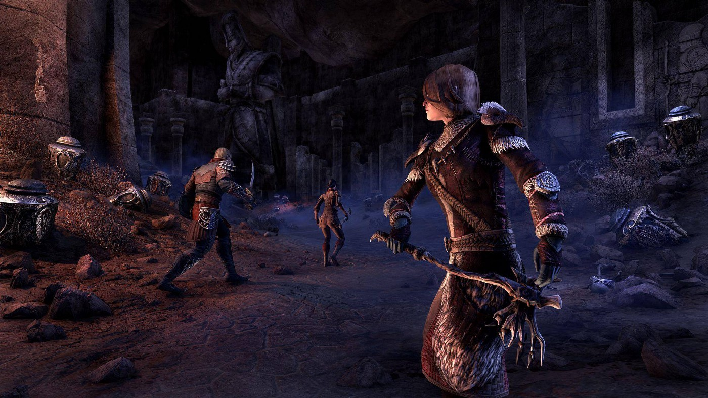 A warrior unsheathes her axe as her compatriots head into a crumbling underground grave full of urns and statues