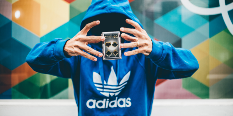 A man in a blue hoodie performing a magic trick with a deck of cards—How I Use Unfair Advantages to Succeed as a Content Creator