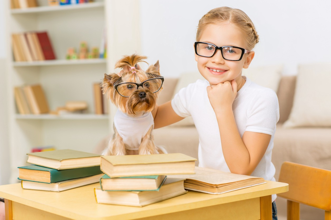 Little girl in glasses with her dog sitting at the desk.