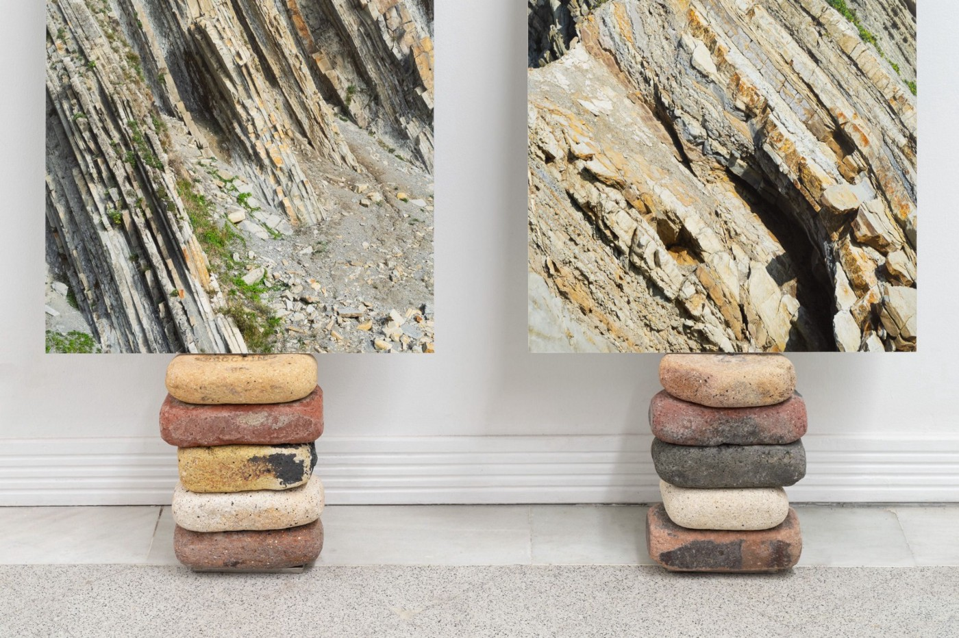 Two totems made of bricks and site-specific materials. They look like two piles of bricks and rocks of different colors with a picture of geological formations on top of each pile.