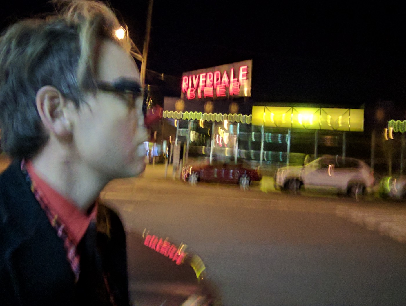 Night time in the Bronx, slightly blurred image of a man wearing a petite red nose and black Buddy Holly glasses in the foreground as he schleps past the blurred neon lights of the Riverdale Diner. He's a medical clown on the way to a bat mitvah.