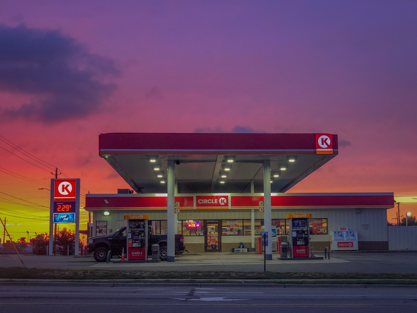 Photo of a Circle K glowing with the light of a beautiful sunset behind it