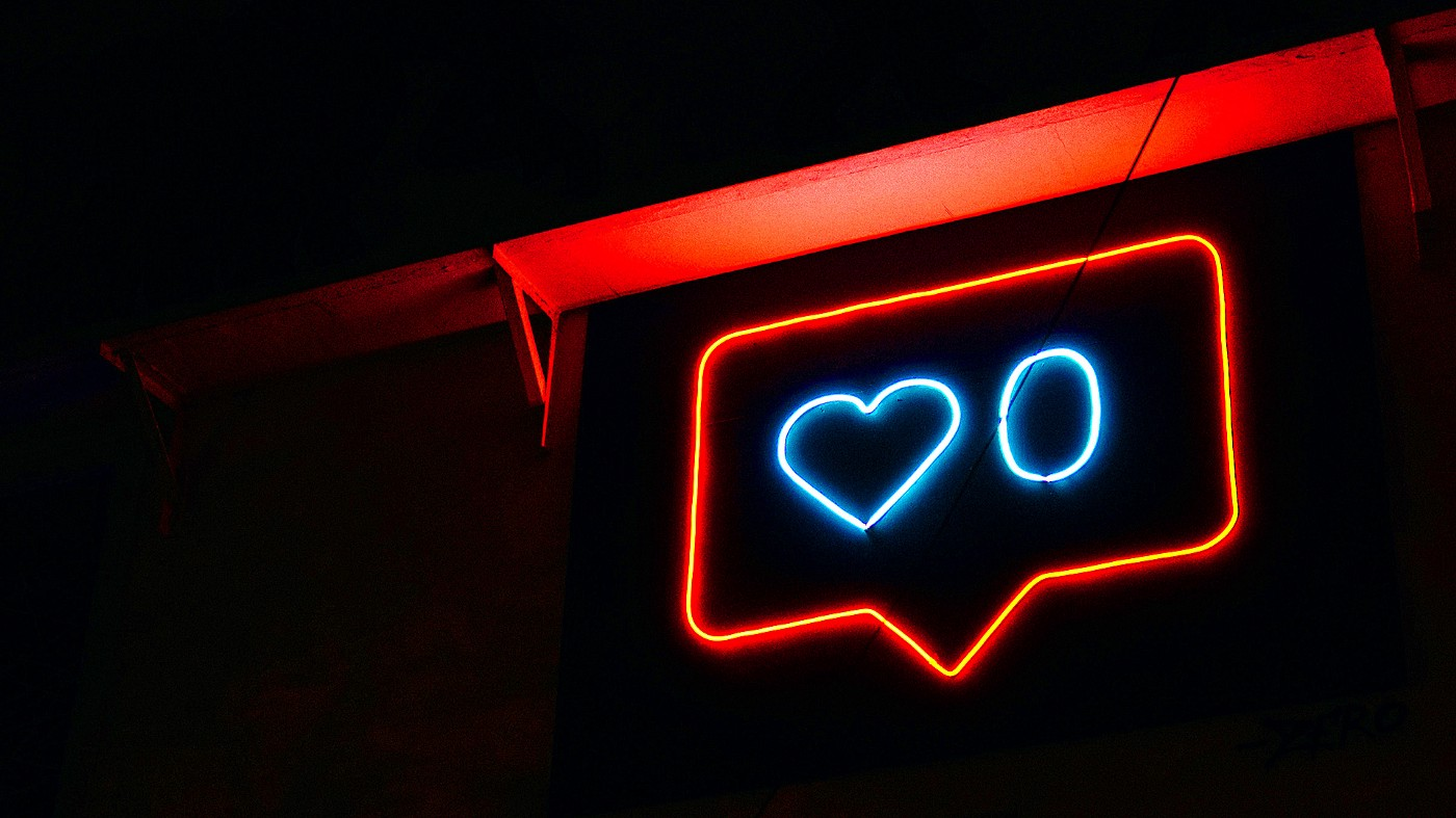 Neon sign in the shape of a like and comment button.