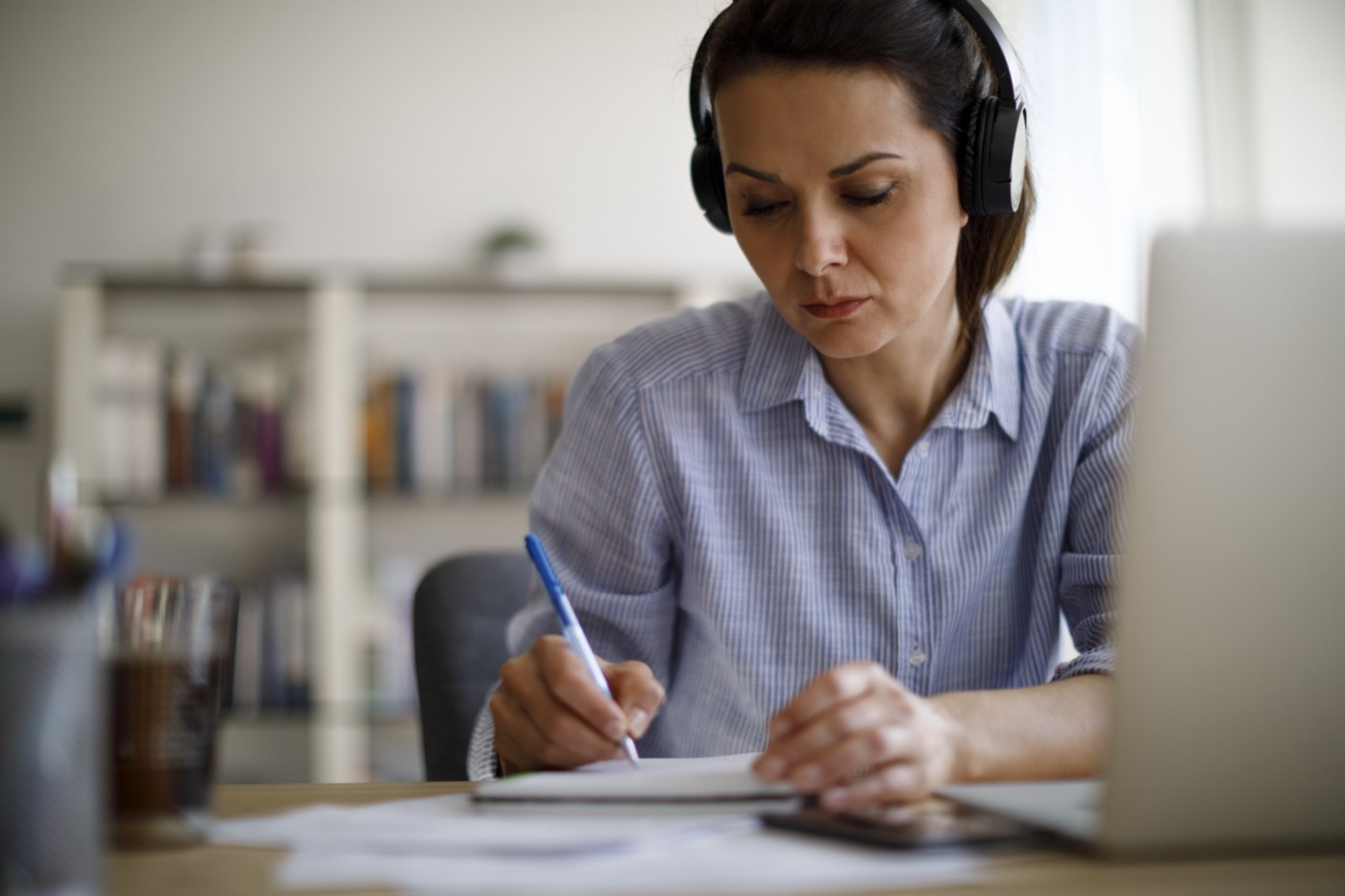 A woman wearing headphones and working on her laptop takes notes.