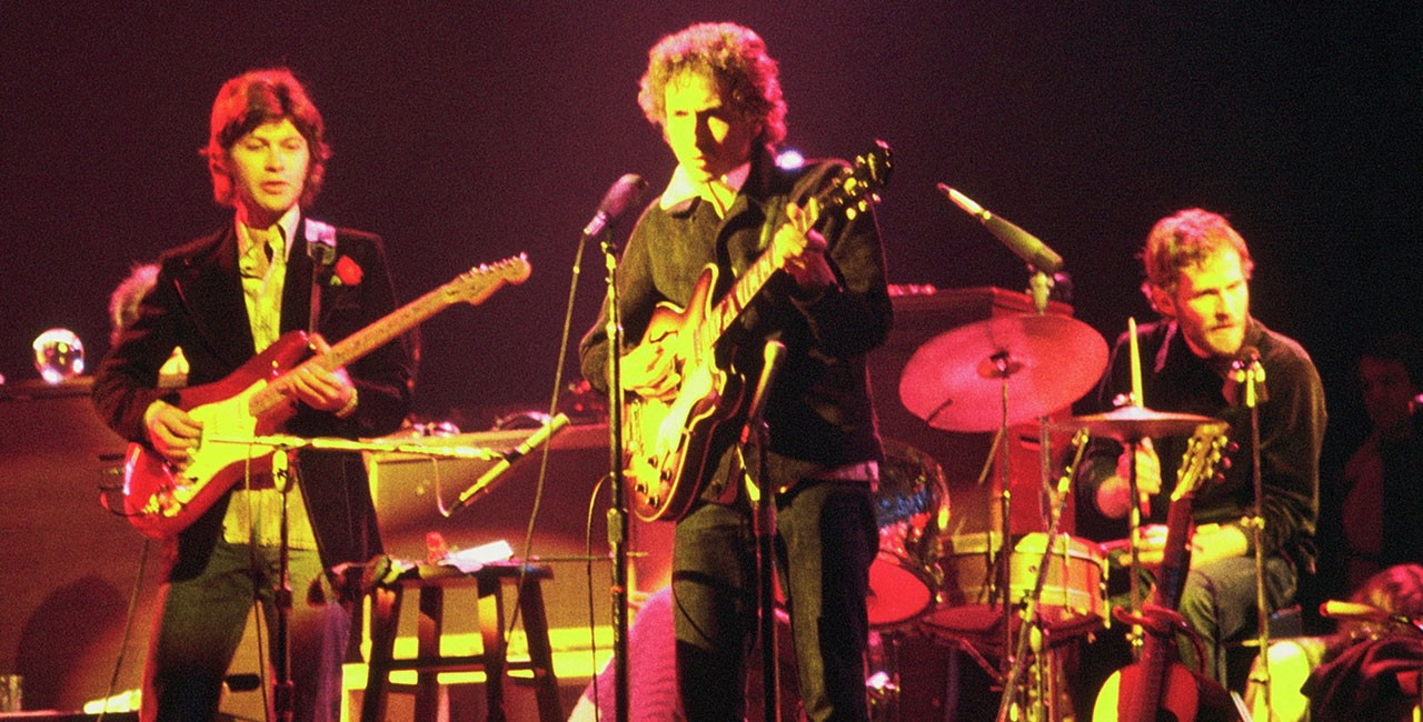 Bob Dylan playing guitar on stage in Chicago in 1974, flanked by Robbie Robertson on guitar and Levon Helm on drums