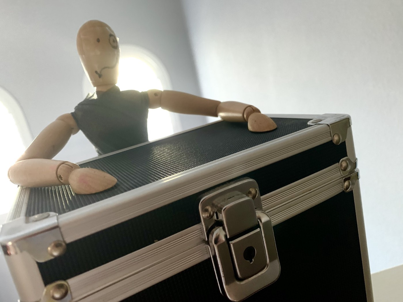 A mannequin stands with her hands on the top of a lockbox.