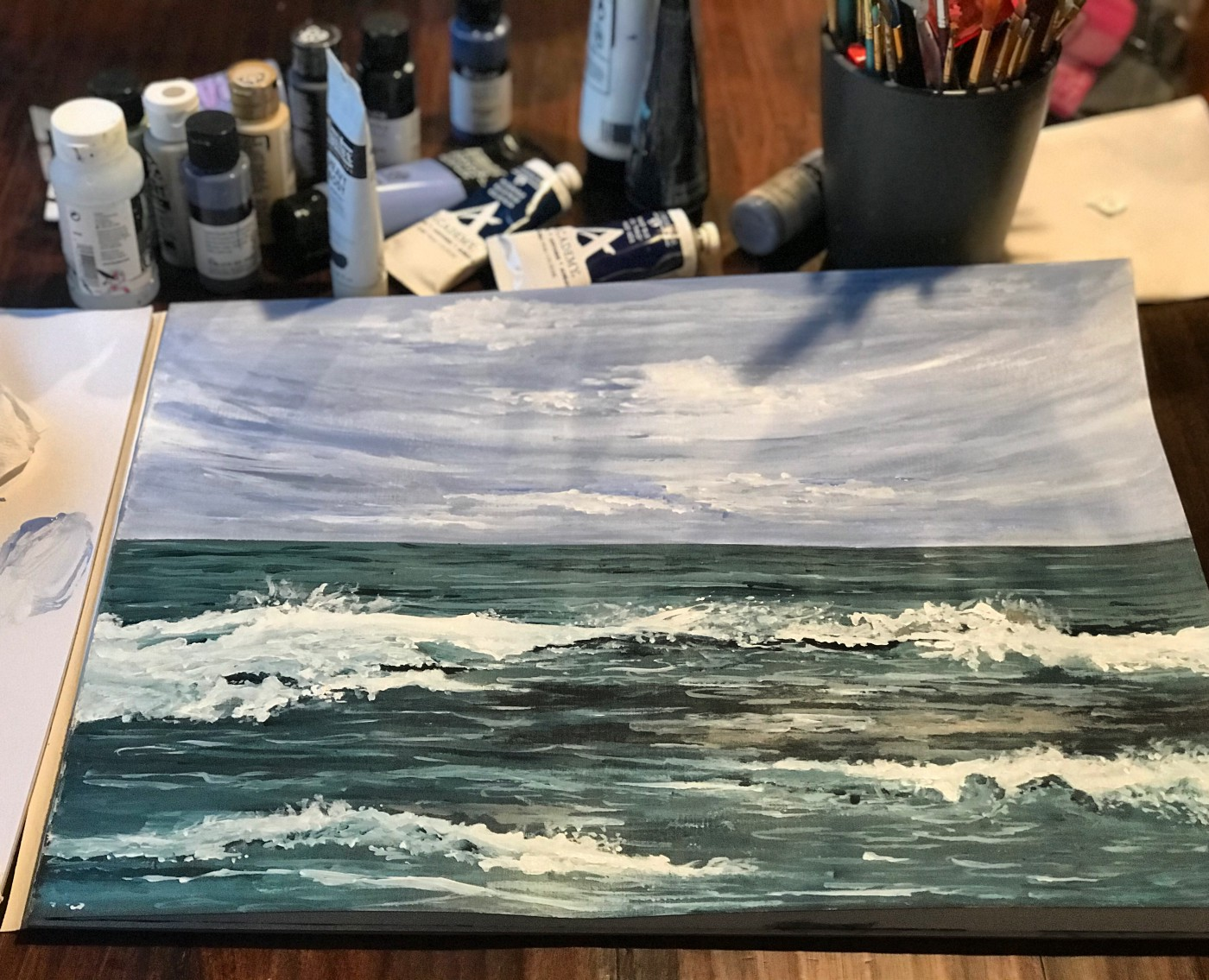 A photo of a painting of the ocean and sky.