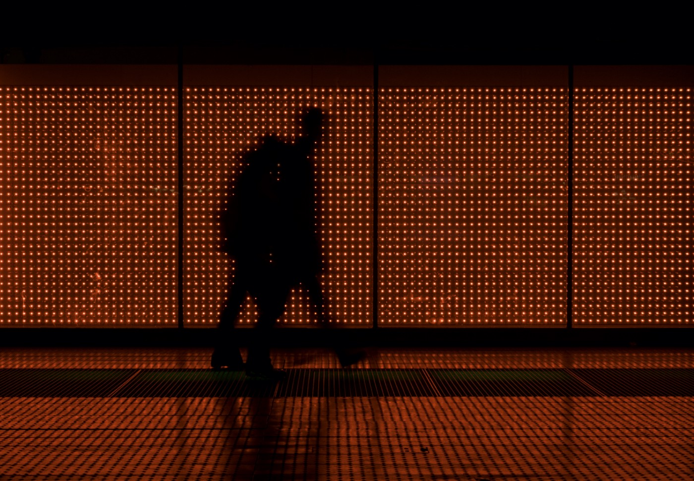 Two people walking, silhouetted against a wall covered with small red lights.