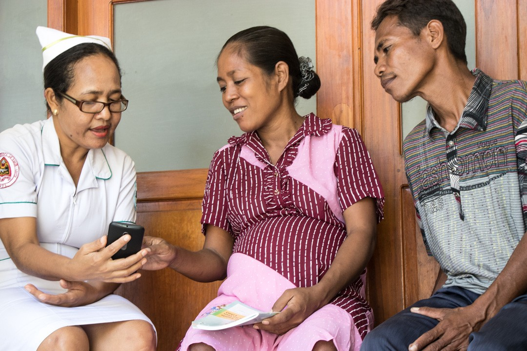 Nurse shows pregnant woman and husband how to use mobile phone for health updates