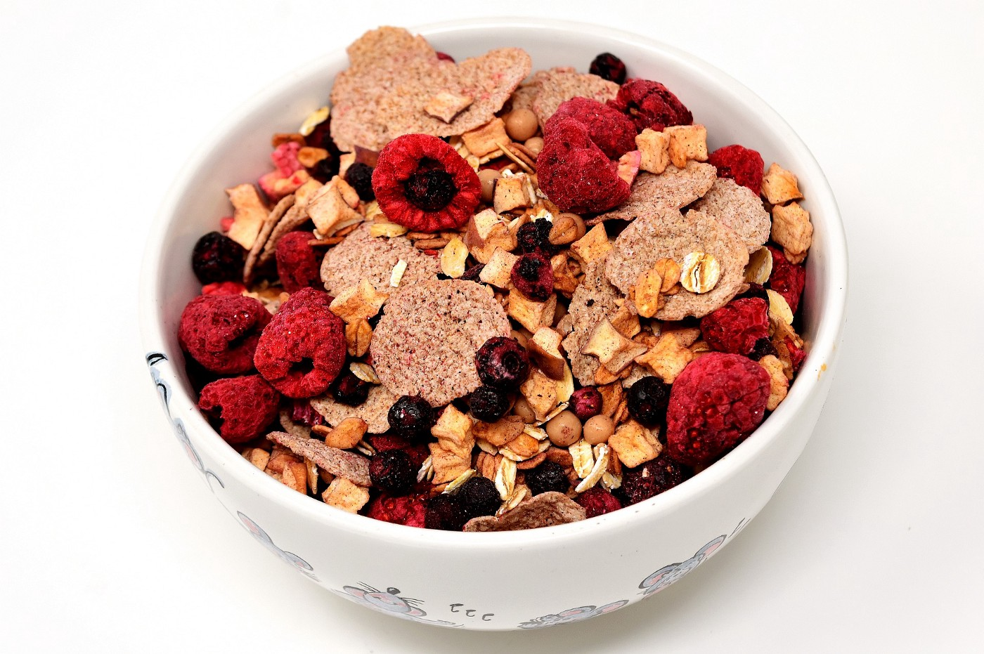 Bowl of muesli cereal with flakes, dried cranberries, fresh raspberries.