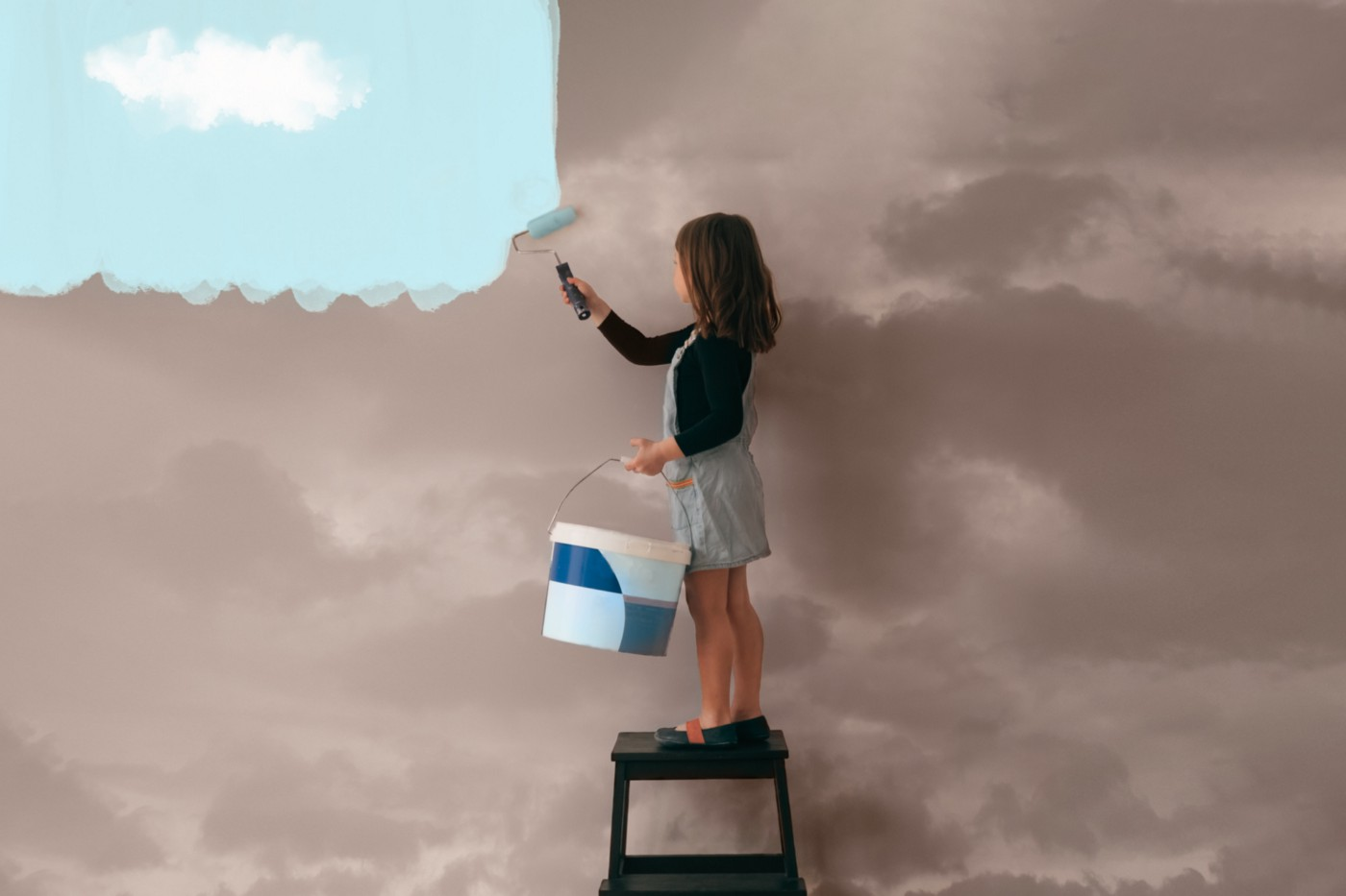A girl paints the wall from a cloudy a clear blue sky.