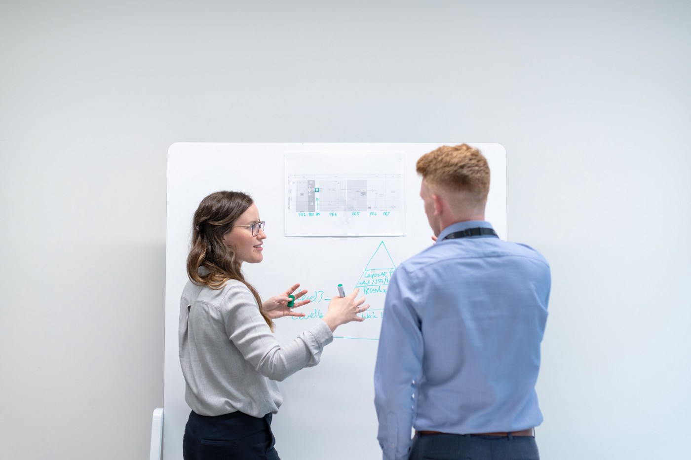 Electronics engineer discusses data in meeting with colleague