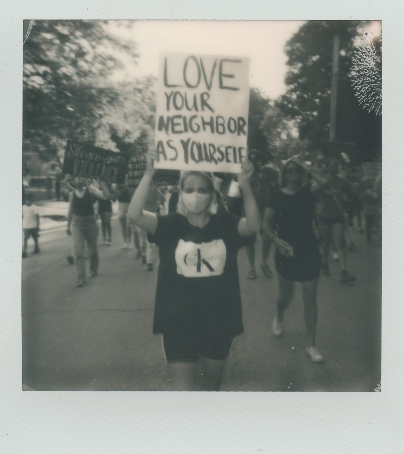 Blurred photo of woman holding up a sign that says love your neighbor as yourself