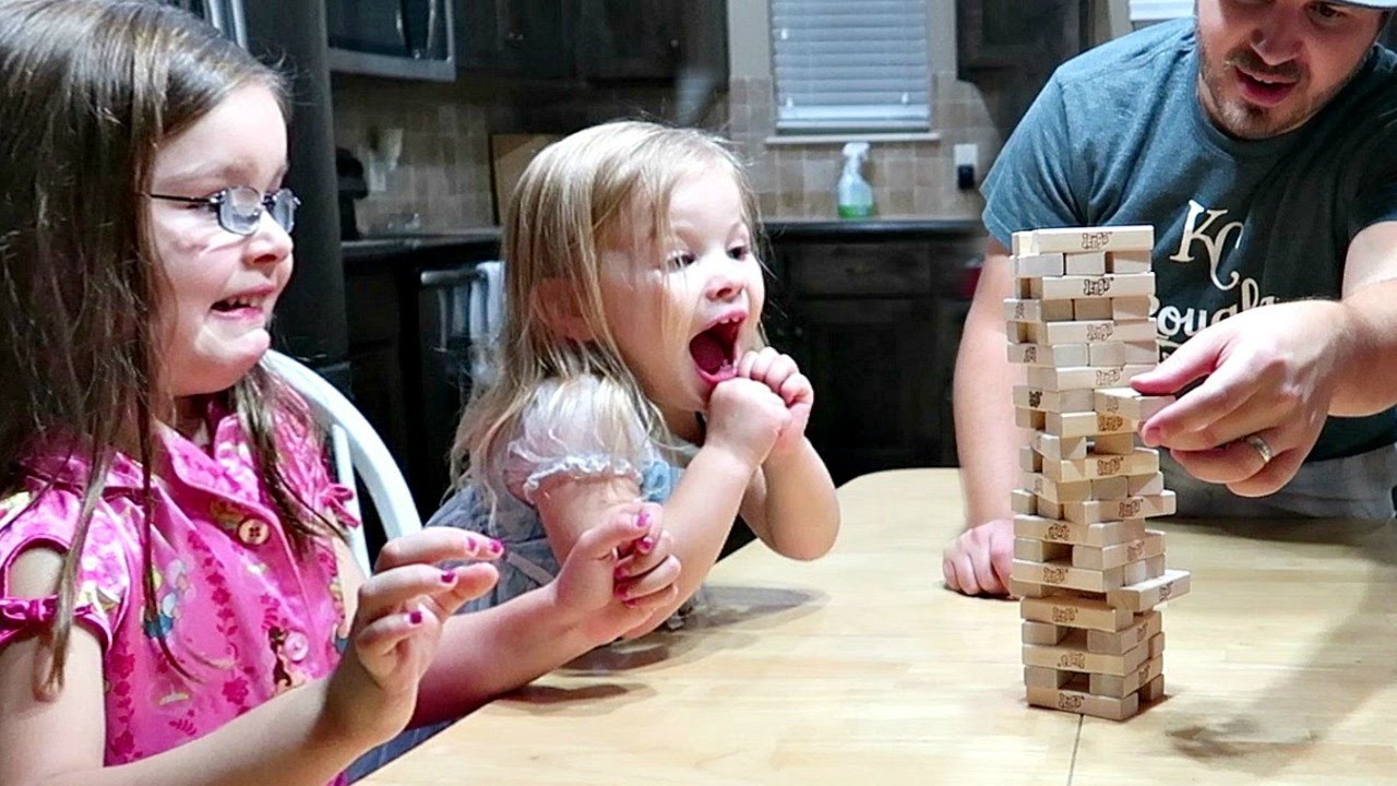 excited girl playing jenga with family