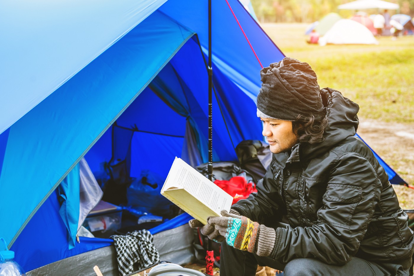 A man camping and reading.
