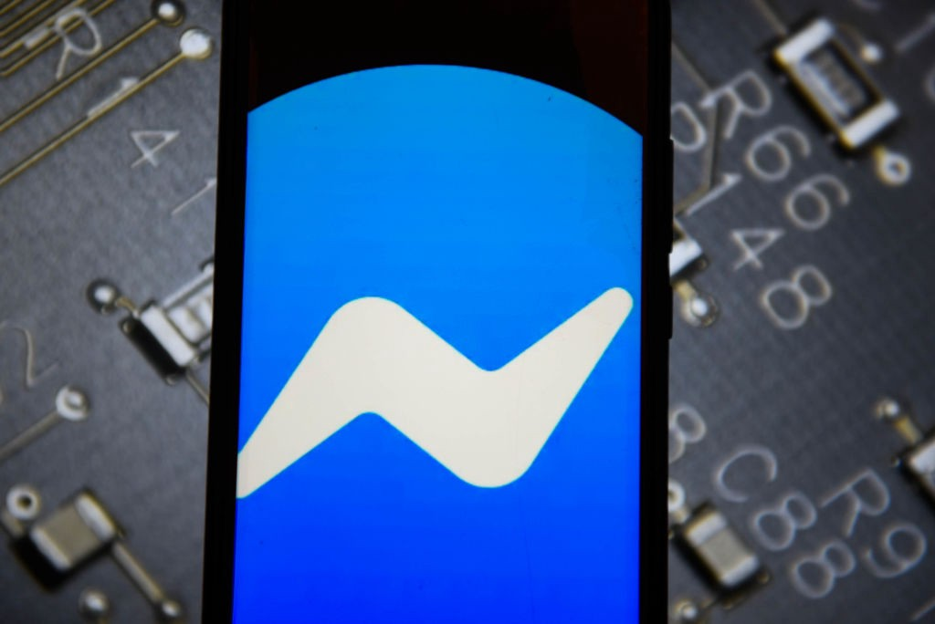 A photo of the Messenger logo on a smartphone with a chip background.