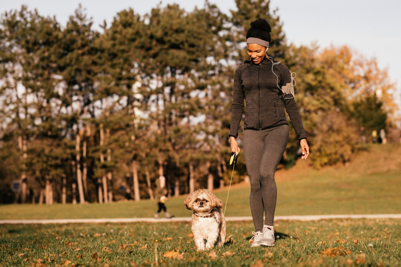 A photo of a black woman walking her dog at a park.