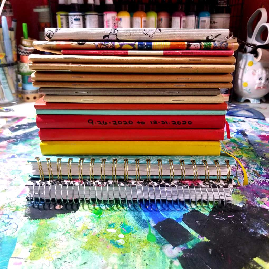 A stack of journals of various colors, sizes, and shapes, that the author completed in 2020.