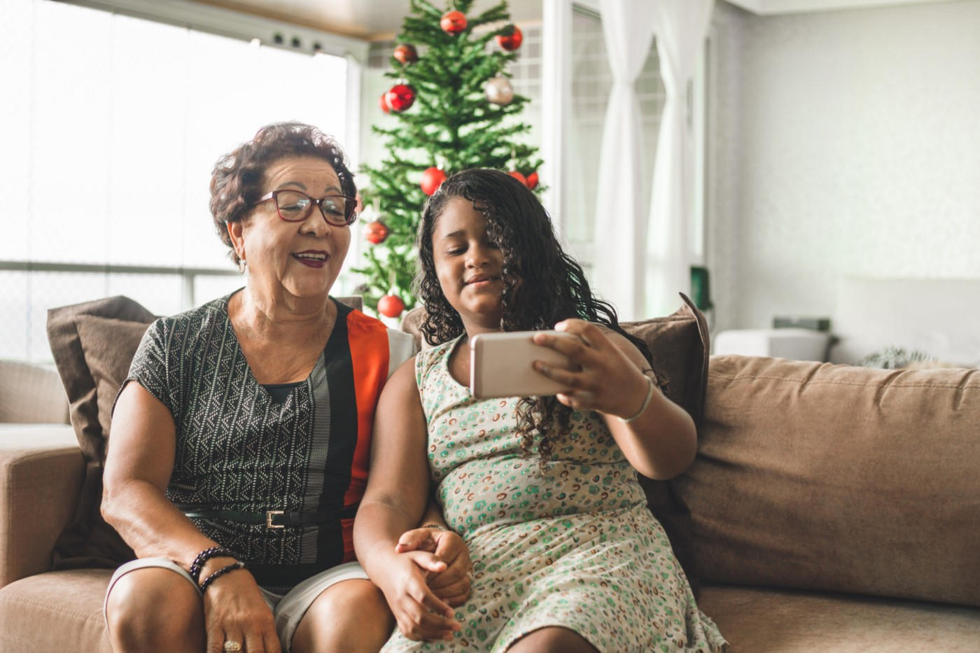 A young girl and her grandmother take a selfie on their couch in front of a Christmas tree.